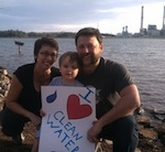 A family poses with a Clean Water sign on the shore of Lake Julian.