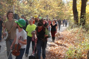 Activists marching through the forest, trees and instruments in hand. (Credit: Climate Ground Zero)