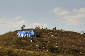 Activists plant trees on reclamation site while others hold banner reading