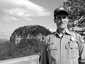 Matt Windsor, park superintendent of Pilot Mountain State Park, stands at Little Pinnacle Overlook, with the Big Pinnacle rising in the background.