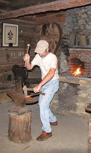 Barry Stiles, curator of the Foxfire Museum, demonstrates blacksmithing skills in a traditional cabin maintained by the Foxfire Fund.