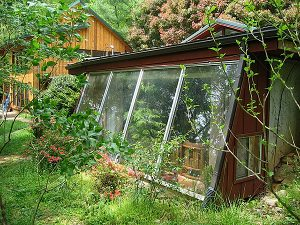 A window into energy efficiency: the south-facing greenhouse soaks up the sun while the earthen sidewalls provide insulation. Photo by Patrick Ironwood
