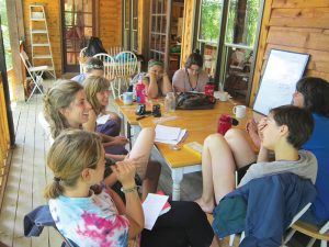 Interns at the New Beginnings camp meet in the afternoons to plan for upcoming days and discuss how to resolve conflicts between campers. Photo by Kimber Ray