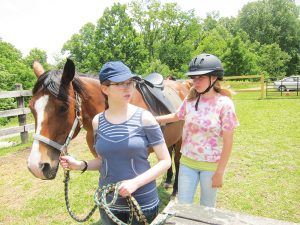 """""""It's about more than riding, that's for sure,"""" explains Nancy Williams, an instructor for the """"connected riding"""" horse class at High Rocks, where the girls learn to be aware of body language. """"If we can't get the lesson through verbally, the horses do it in a non-verbal way."""" Photo by Molly Moore"""