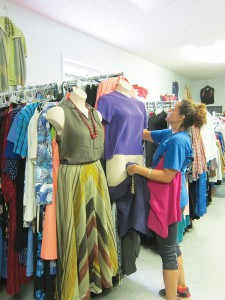 A volunteer at the New Opportunity School's clothing boutique arranges a mannequin display. The boutique supplies the school's graduates with free business appropriate outfits, and also employs graduates from the program. Photo by Molly Moore