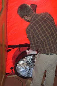 John Kidda, a home energy contractor, prepares a blower door test at Sean Dunlap's home. Photo by Eliza Laubach