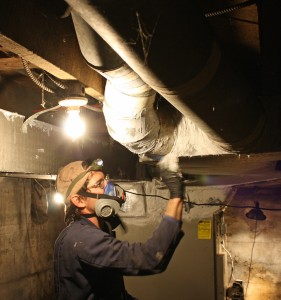 Will Hadaway, owner of HomEfficient, seals Vance Woodie's basement ducts with mastic.