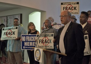 Rev. Hairston, president of the Stokes County, N.C., NAACP, speaks at an event to bring attention to disproportionate environmental threats in low-income communities of color. At left, a concerned resident holds a sign asking for the state to designate Belews Creek as a high-priority coal ash cleanup site.