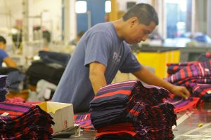 A worker-owner arranges fabric at the Opportunity Threads plant in Morganton, N.C.  Photo by Willa Johnson