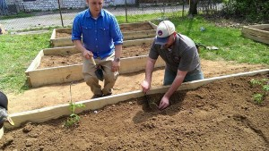Veteran Logan Nance, director of operations at Growing Warriors, plants in a raised bed with a community member. Photo courtesy of Growing Warriors