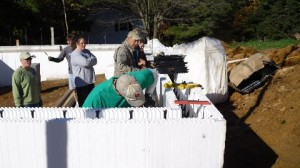 A group of volunteers for Ashe County Habitat for Humanity set foam blocks into place. Concrete will be poured over the blocks to create an airtight wall.