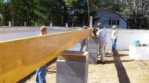 A group of volunteers for Ashe County Habitat for Humanity lays a timber frame on their first house, which was built with energy efficiency and alternative energy to lessen the burden of utility bills on people living in poverty.