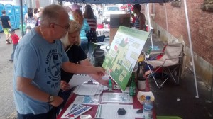 Violet Scholar, a volunteer from Lansing, N.C., explains on-bill financing and energy efficiency at a tabling event.