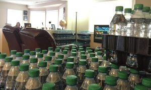 Bottles of water sit in stacks in Amy Brown's living room. She is now familiar with how many bottles are needed for each family meal — boiling spaghetti takes four, while only two are needed for rice.
