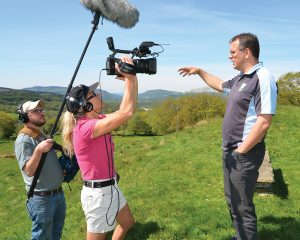 Filmmaker Tom Hansell and camera person Suzanne Clouseau interview Geraint Lewis near Abercraf, Wales. The company Lewis started, Call of the Wild, has repurposed an old farm and created a leadership development center. Photo by Mair Francis