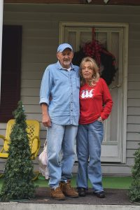 Karen and Jerry Kirk stand on the front porch of their home. Their property damage coincided with blasting at a mountaintop removal coal mine associated with the King Coal Highway. Photo by Molly Moore