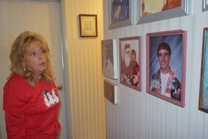 Karen Kirk points out photographs of their sons, who all live out of the area now. She says it is unlikely that they will move back to Mingo County.  Photo by Molly Moore