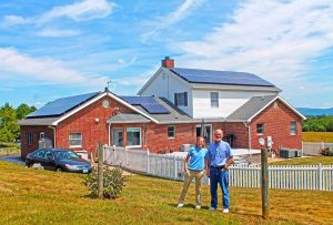 Augusta Solar Co-op member and homeowner Keith Shank stands with a representative of the solar installation company in front of his new solar array. Photo courtesy VA SUN