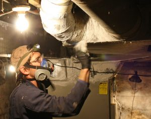 Will Haddaway, owner of HomEfficient, seals Blue Ridge Electric member Vance Woodie's leaky air ducts before insulating them.