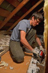 A High Country Energy Solutions employee weatherizes Sean Dunlap's home.