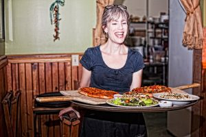 Harvest Table's menu features well-crafted standards like stone-oven pizzas, pasture-raised meats, and vegetarian and vegan offerings. Photo courtesy of 621studios.com