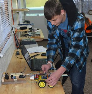 Elijah Kiser adjusts the robotic car at the Clintwood Learning Co-op.