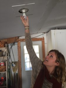Volunteer Kaytlin Hester-Newnam installs an energy efficient LED light bulb. Photo: Ridge Graham