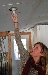 volunteer installing lightbulb