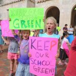 "Two female students holding signs that say ""Keep our school green"""
