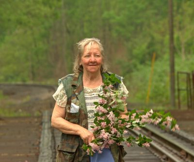 Carol Judy carries branches of flowers in Bell County, Ky. Photo by Joanne Golden Hill.