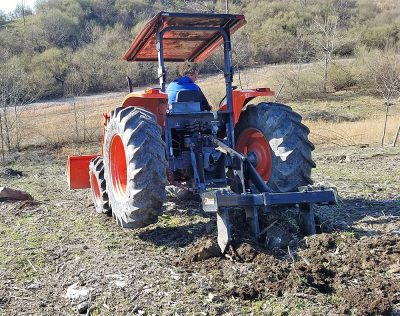 Woman on tractor breaking up soil