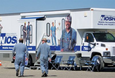 Miners walk to a mobile health screening unit operated by the National Institute for Occupational Safety and Health. Photo courtesy of CDC-NIOSH