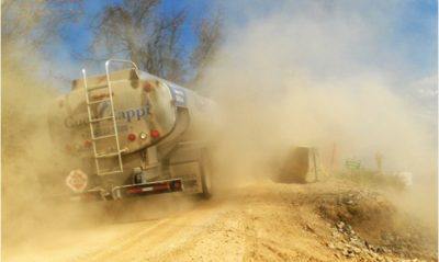 Heavy traffic to and from a fracking well pad causes a dust cloud along a small roadway in West Virginia. Aug. 15, 2014. Photo courtesy of The FracTracker Alliance, www.fractracker.org/photos