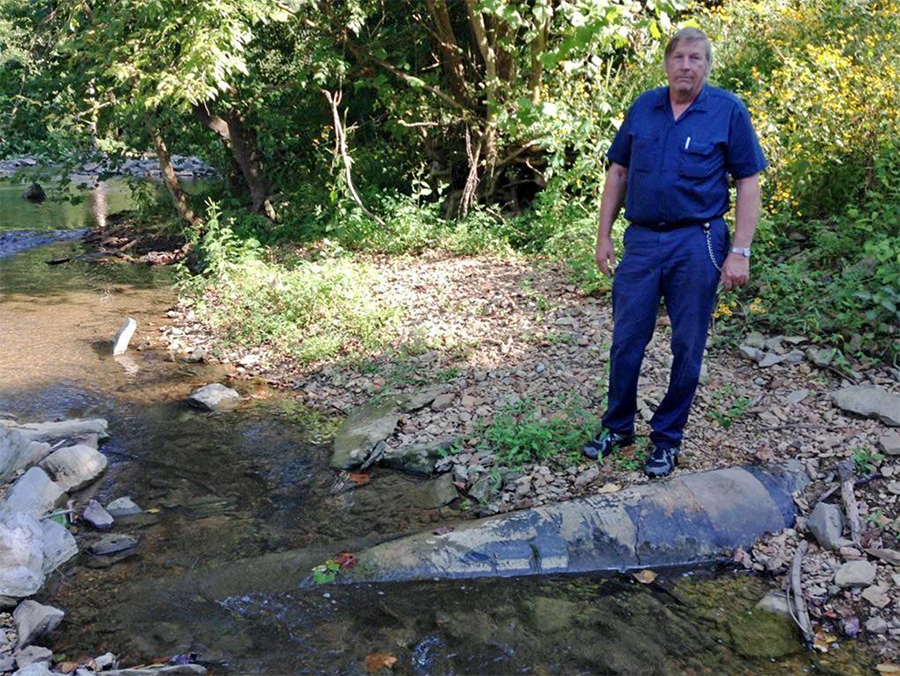 "John Henry Armstrong, III, co-author of the ""2015 Field Study Of Gas Pipeline Safety In Tennessee"" study, standing by a partially buried and eroding pipeline in a Tennessee stream"