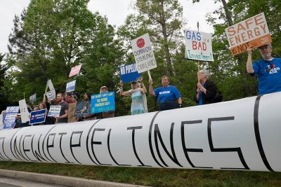 "people stand with ""no pipelines"" signs"