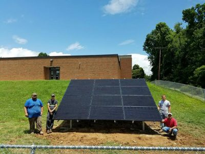 Crew members and completed solar installation.