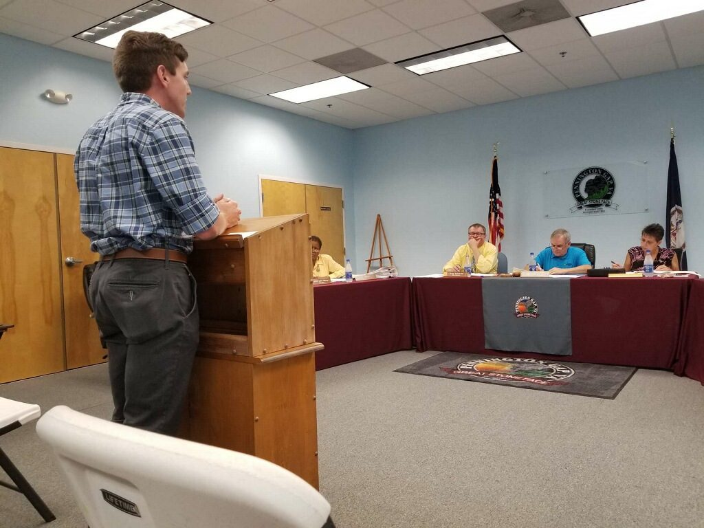 man speaking to town council
