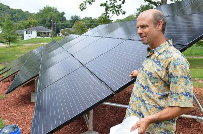 A man stands with solar panels