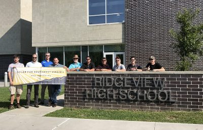 Members of solar workgroup stand outside a high school