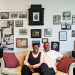 Two people sit on couch in front of wall of photos and documents