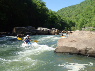 Two kayakers navigate a rapid
