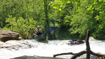 man in a canoe goes over a rapid