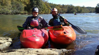 Two kayakers on the water smile for the camera
