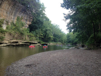 Two kayaks paddle on a river past a large rock wall