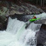 kayaker paddles over a ten foot waterfall