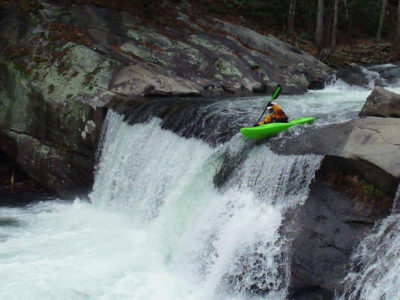 kayaker paddles over a ten foot waterfall