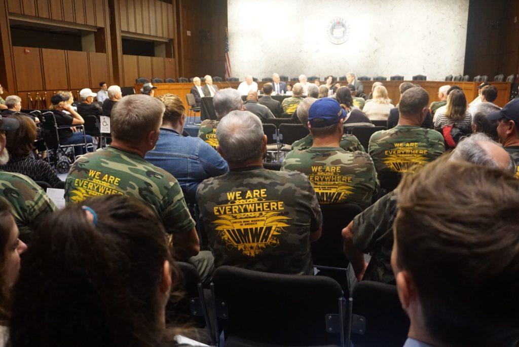 miners in UMWA shirts sit in Senate hall