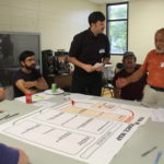 Participants gather around a table with large sheets of paper
