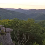 green mountains stretch into the horizon at dusk