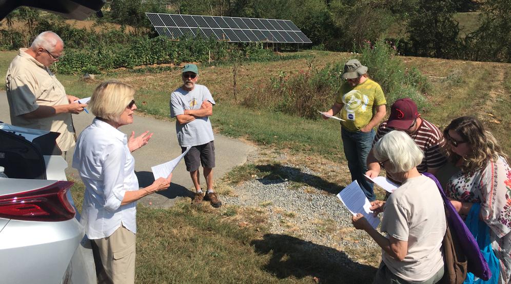 people speaking by solar panels